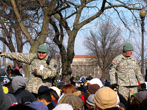 Military directing large crowd